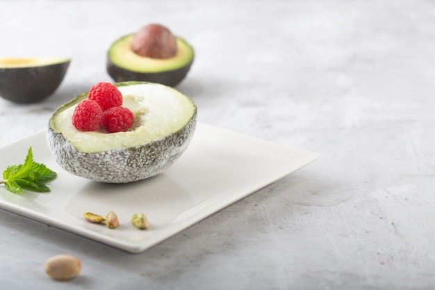 Hausgemachtes bio-avocado- und pistazieneis mit himbeeren
