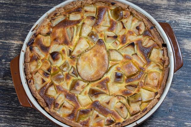 Hausgemachtes bio-birnenkuchen-dessert essfertig. birnentorte auf dem alten hölzernen hintergrund, nahaufnahme. schöne bio-frucht-torte mit glutenfreier kruste