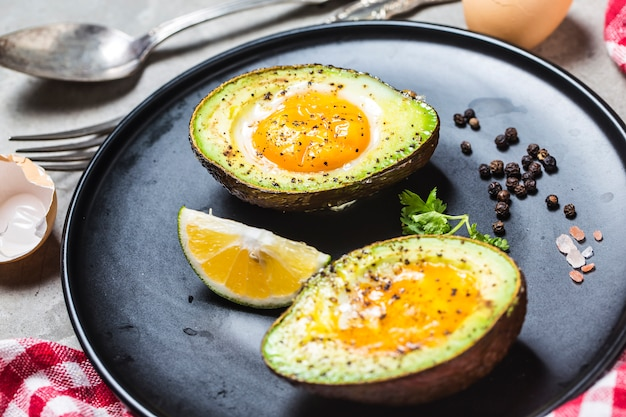 Hausgemachtes bio-ei gebacken in avocado mit salz und pfeffer