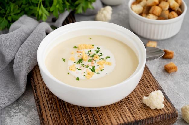 Hausgemachtes blumenkohlsuppenpüree in einer weißen schüssel mit käse-sahne-gewürzen und frischer petersilie o