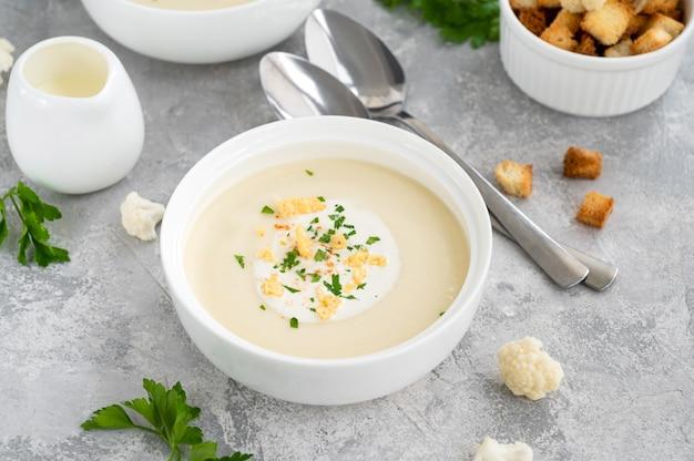 Hausgemachtes blumenkohlsuppenpüree in einer weißen schüssel mit käse-sahne-gewürzen und frischer petersilie
