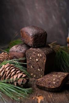 Hausgemachtes braunes fermentiertes brot mit zedernnüssen auf dunklem holzhintergrund