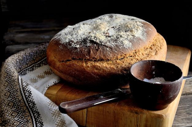 Hausgemachtes brot auf dem küchentisch, salz, serviette, messer und küchenschneidebrett.