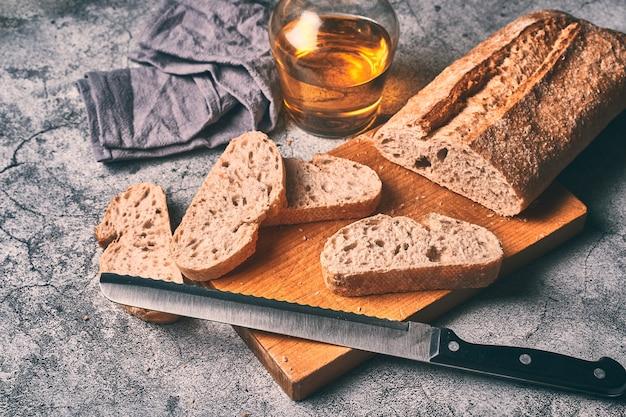 Hausgemachtes brot auf einem holzbrett zusammen mit einer flasche olivenöl extra vergine geschnitten. traditionelles mediterranes frühstückskonzept.