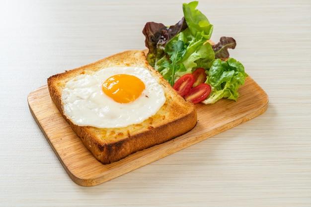 Hausgemachtes brot geröstet mit käse und spiegelei obenauf mit gemüsesalat zum frühstück