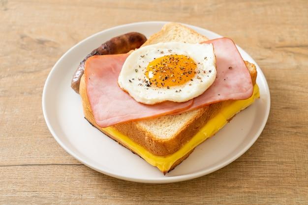 Hausgemachtes brot gerösteter käse überbackener schinken und spiegelei mit schweinswurst zum frühstück