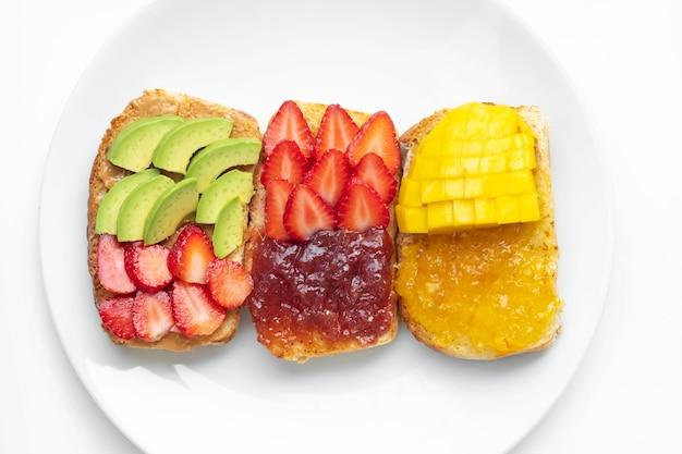 Hausgemachtes brot mit erdnussbutter, orangenmarmelade und erdbeermarmelade mit erdbeeren, mango und avocado auf weißem teller. gesundes essen zum abnehmen. gesundes frühstückskonzept.