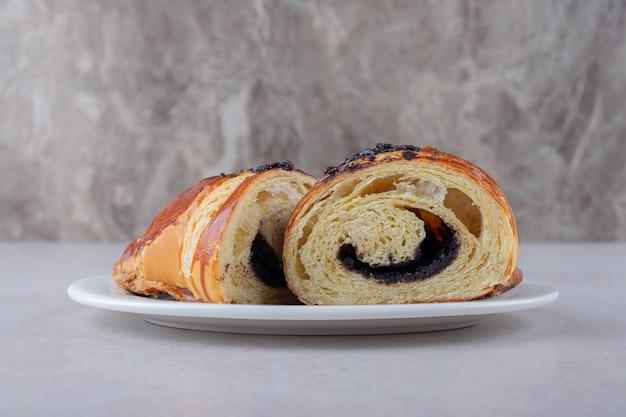 Hausgemachtes croissant in scheiben geschnitten mit schokolade auf einem teller auf marmortisch.