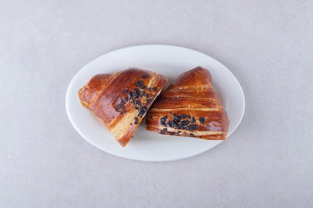 Hausgemachtes croissant in scheiben mit schokolade auf einem teller, auf dem marmor.