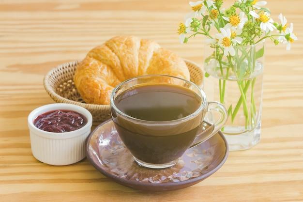 Hausgemachtes croissant serviert mit schwarzem kaffee oder americano und erdbeermarmelade zum frühstück