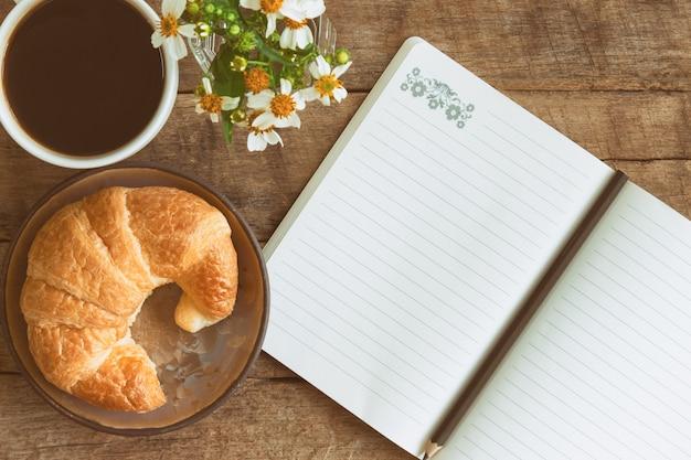 Hausgemachtes croissant serviert mit schwarzem kaffee oder americano zum frühstück oder kaffeepause.