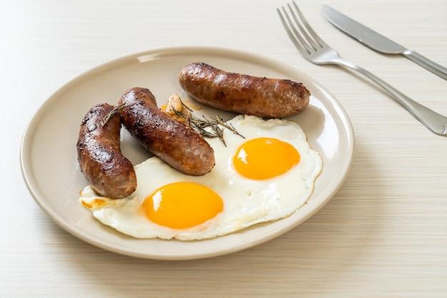 Hausgemachtes doppeltes spiegelei mit gebratener schweinswurst - zum frühstück