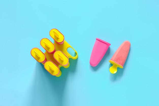 Hausgemachtes eis am stiel. natürliches erdbeereis in hellen plastikformen