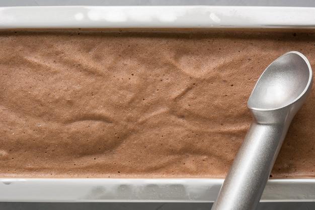 Hausgemachtes eis der bananenschokolade im behälter mit kaffeebohnen auf schwarz. draufsicht.