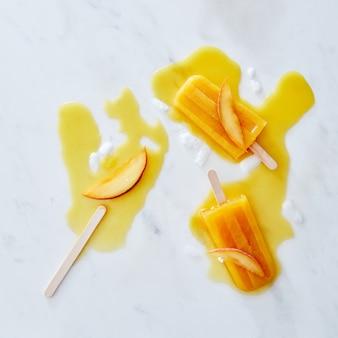 Hausgemachtes eis oder eis am stiel von einer pfirsichscheibe, die auf einem marmorhintergrund verziert wird. draufsicht. sommerstimmung.