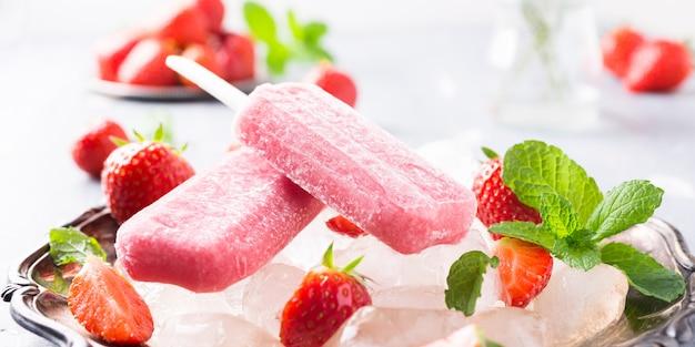 Hausgemachtes erdbeer-eis am stiel
