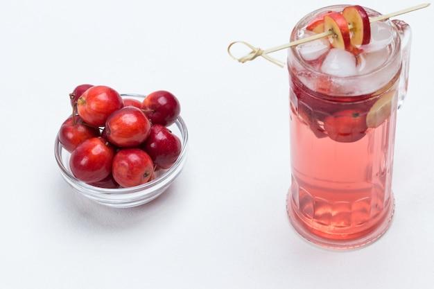 Hausgemachtes erfrischendes sommerapfelgetränk mit eis im glas. geschnittene äpfel am stiel. kleine rote äpfel in glasschale. weißer hintergrund. draufsicht.