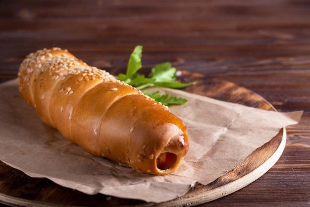 Hausgemachtes essen hotdog, wurst im teig auf holzteller auf holztisch kopierraum