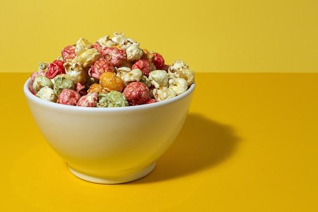 Hausgemachtes farbiges popcorn auf farbigem tisch mit kontrastreichem licht. snack-konzept