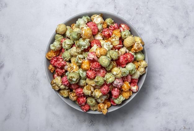Hausgemachtes farbiges popcorn auf marmortisch mit kontrastreichem licht. snack-konzept