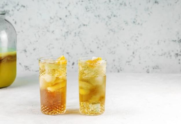 Hausgemachtes fermentiertes kombucha-getränk mit eis und einer scheibe mandarine