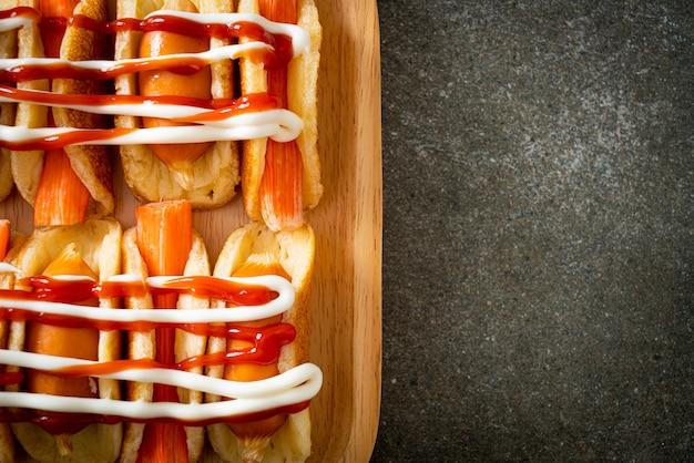 Hausgemachtes flaches pfannkuchenbrötchen mit wurst und krabbenstäbchen