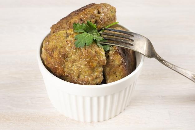 Hausgemachtes fleisch rindfleisch burger pastetchen schnitzel auf weißer schüssel auf tisch mit gabel und kräutern. ketogenes fleischfresser-diätkonzept. nahansicht. selektiver fokus. speicherplatz kopieren
