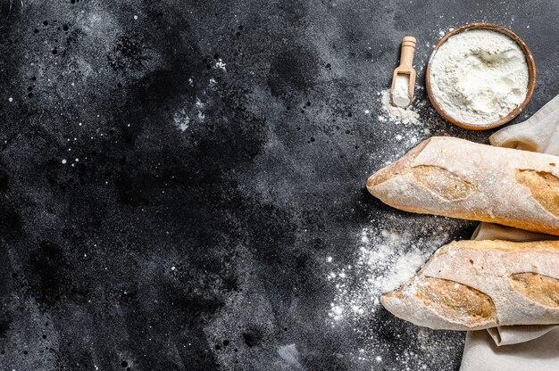 Hausgemachtes französisches baguettebrot. das konzept des brotkochens. schwarzer hintergrund. draufsicht. speicherplatz kopieren