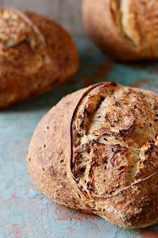 Hausgemachtes frisch gebackenes landbrot aus weizen und vollkornmehl auf dunkler oberfläche. französisch frisch gebackenes brot.