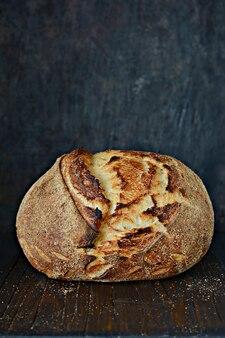 Hausgemachtes frisch gebackenes landbrot, hergestellt von weizen und vollkornmehl auf einem dunklen hintergrund. französisch frisch gebackenes brot. hausgemachtes brot schneiden