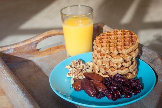 Hausgemachtes frühstück - haferflockenwaffeln mit getrockneten früchten, nüssen und saft.