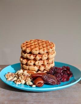 Hausgemachtes frühstück - haferflockenwaffeln mit getrockneten früchten und nüssen