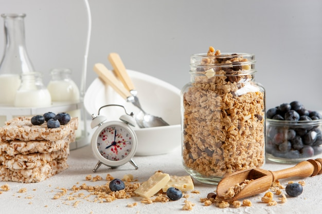 Hausgemachtes frühstücksmüsli, müsli mit frischen reifen heidelbeeren, weißer schokolade, mehrkornkuchen und milch