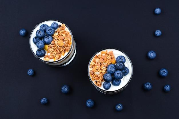 Hausgemachtes gebackenes müsli mit joghurt und blaubeeren in einem glas auf einem schwarzen hintergrund. platz für text oder design.