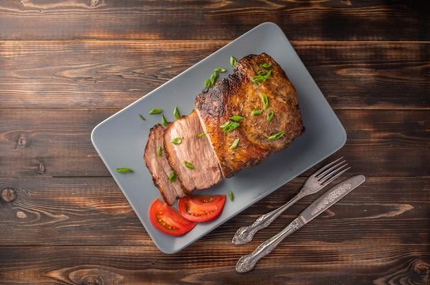Hausgemachtes gebackenes schweinefleisch mit gemüse und gewürzen auf einem servierbrett auf einem hölzernen hintergrund.