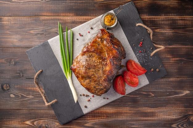 Hausgemachtes gebackenes stück fleisch mit gemüse und gewürzen auf einem servierbrett auf einem hölzernen hintergrund.