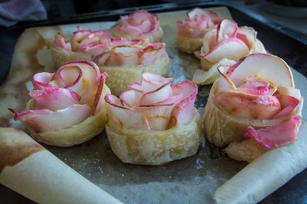 Hausgemachtes gebäck. apples rosen aus blätterteig auf einem backblech.