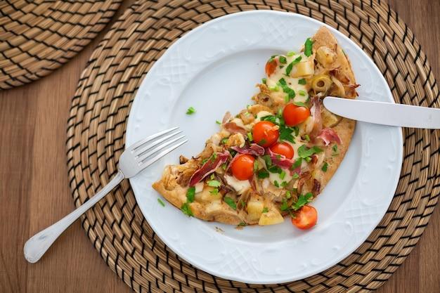 Hausgemachtes gefülltes omelett mit tomaten, kartoffeln, oliven, speck und viel käse. gesundes und leckeres essen zum frühstück. draufsicht, flach liegen.