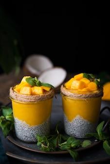 Hausgemachtes gesundes frühstück, chia pudding mit kokosmilch und mango auf einem holztisch