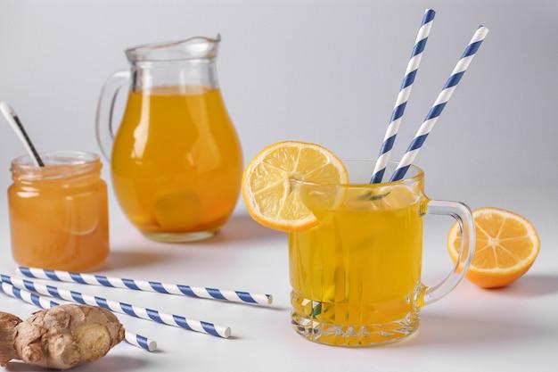 Hausgemachtes gesundes getränk mit zitrone, ingwer, honig und kurkuma auf einer weißen oberfläche, horizontale ausrichtung, nahaufnahme
