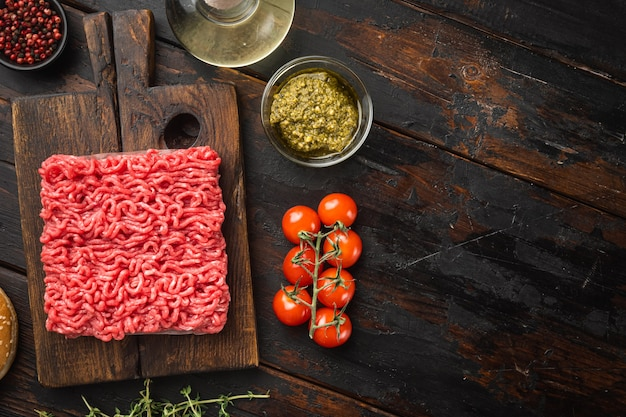 Hausgemachtes hackfleisch in einer schwarzen schüssel mit zutaten. frisches rohes hackfleisch zum kochen von fleischbällchen gesetzt, auf altem dunklem holztisch, draufsicht flach gelegt