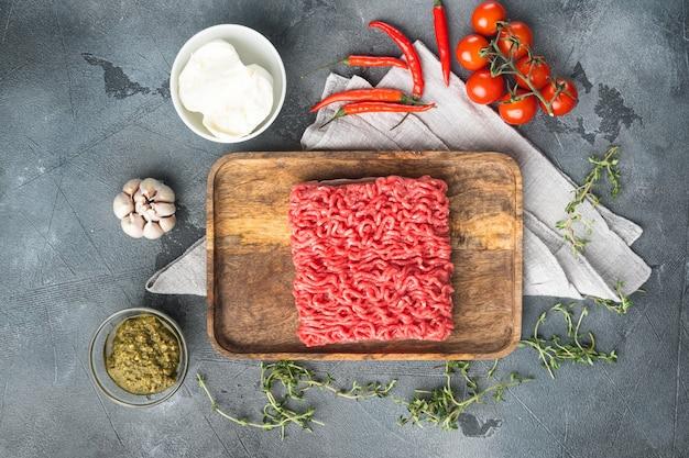 Hausgemachtes hackfleisch in einer schwarzen schüssel mit zutaten. frisches rohes hackfleisch zum kochen von fleischbällchen gesetzt, auf grauem steintisch, draufsicht flach gelegt