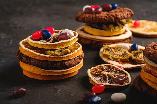 Hausgemachtes hafer-schokoladen-kekssandwich mit getrockneten zitrusfrüchten und saftigen gummibärchen