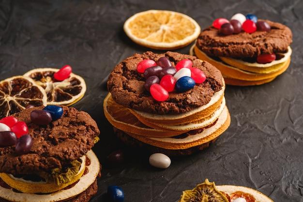 Hausgemachtes haferschokoladenplätzchensandwich mit getrockneten zitrusfrüchten und saftigen gummibärchen auf strukturiertem dunkelschwarzem hintergrund, winkelansicht