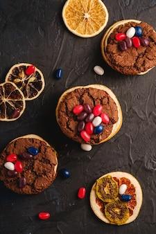 Hausgemachtes haferschokoladenplätzchensandwich mit getrockneten zitrusfrüchten und saftigen gummibärchen auf strukturierter dunkelschwarzer oberfläche, draufsicht