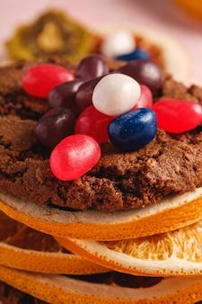 Hausgemachtes haferschokoladenplätzchensandwich mit getrockneten zitrusfrüchten und saftigen gummibärchen auf strukturierter rosa oberfläche, winkelansicht-makro