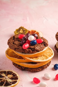 Hausgemachtes haferschokoladenplätzchensandwich mit getrockneten zitrusfrüchten und saftigen gummibärchen auf strukturierter rosa oberfläche, winkelansicht