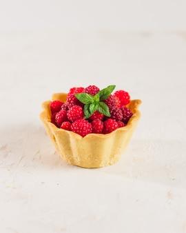 Hausgemachtes himbeergebäck. sommerbeeren-minitörtchen mit vanillepudding und minzblättern. frische desserts auf dem weißen hintergrund lokalisiert. freier kopierplatz.