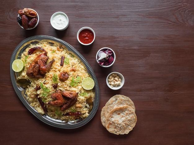 Hausgemachtes huhn biryani. arabische traditionelle futternäpfe kabsa mit fleisch. draufsicht, kopierraum