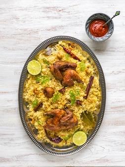 Hausgemachtes huhn biryani. arabische traditionelle futternäpfe kabsa mit fleisch. draufsicht